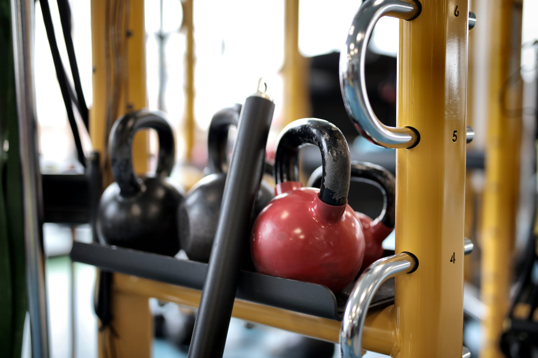 several kettlebells on metal bar in gym